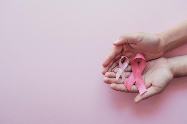 Mãos segurando fitas cor de rosa em fundo rosa
