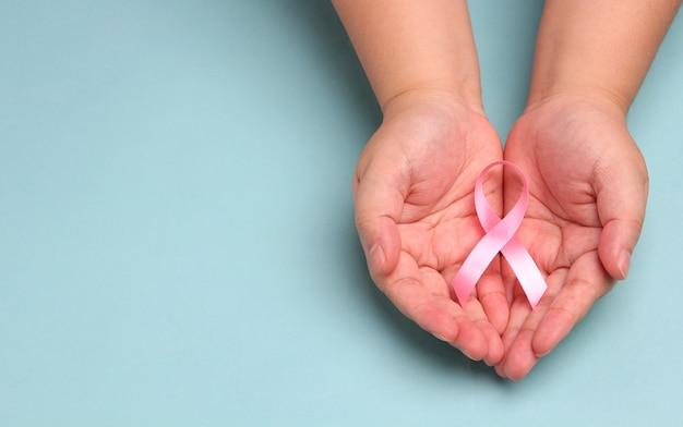 Mãos segurando fitas rosa sobre fundo azul.