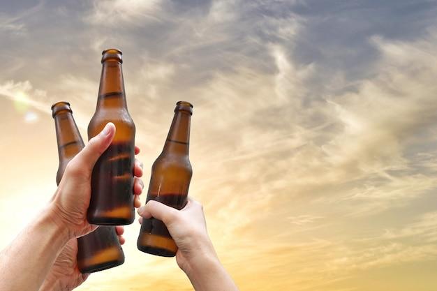 Mãos, segurando, garrafas cerveja, e, feliz, desfrutando, tempo colheita, junto, para, tinindo, óculos, em, partido ao ar livre