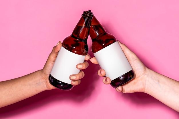 Mãos segurando garrafas de cerveja contra um fundo rosa