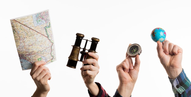 Mãos segurando itens de viagem com mapa e bússola