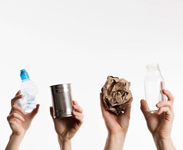 Mãos segurando itens recicláveis