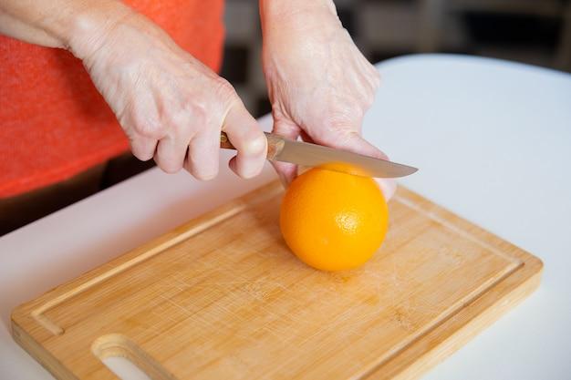 Mãos segurando laranja e cortá-lo com faca