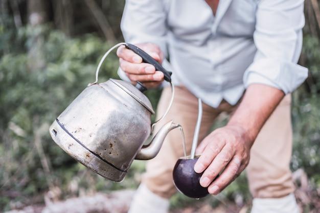Mãos segurando mate e bule para beber erva-mate tradição argentina.