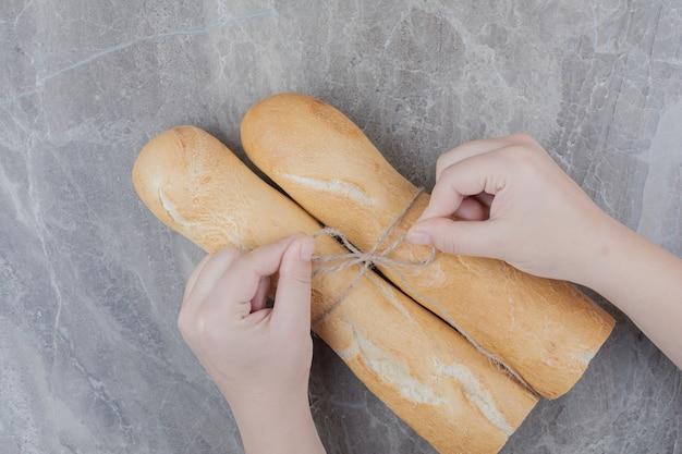 Mãos segurando meio corte de pão baguete francês em superfície de mármore
