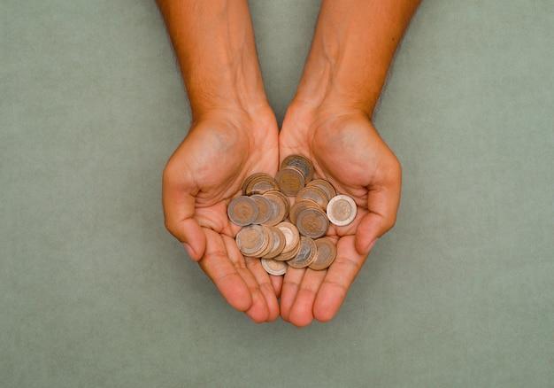 Mãos segurando moedas.