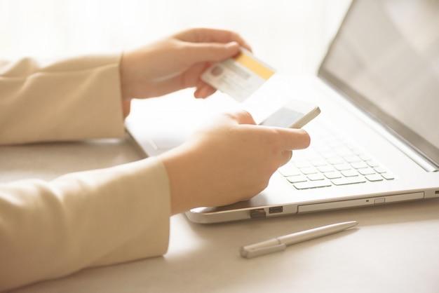 Mãos segurando o cartão de crédito e smatrphone. onine compras.