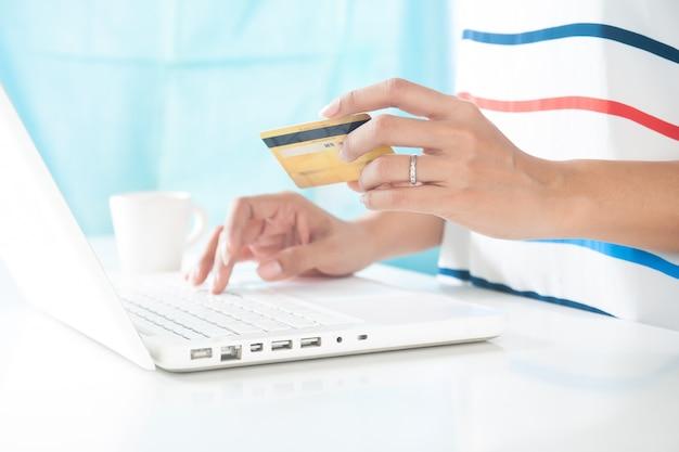 Mãos segurando o cartão de crédito e usando o computador portátil. compras on-line, e-pagamento ou internet banking