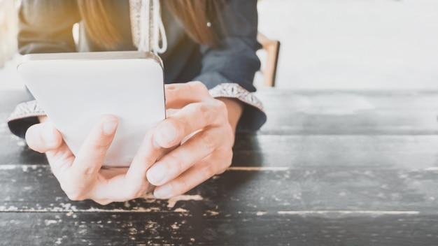 Mãos segurando o smartphone no café.