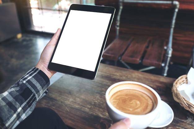 Mãos segurando o tablet pc preto com tela branca em branco enquanto bebe café