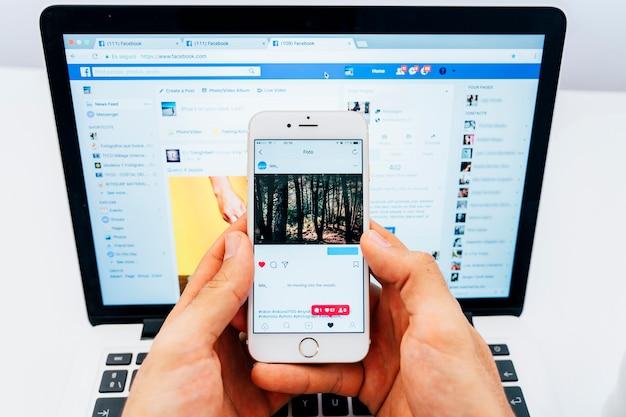 Mãos segurando o telefone com instagram e laptop com facebook