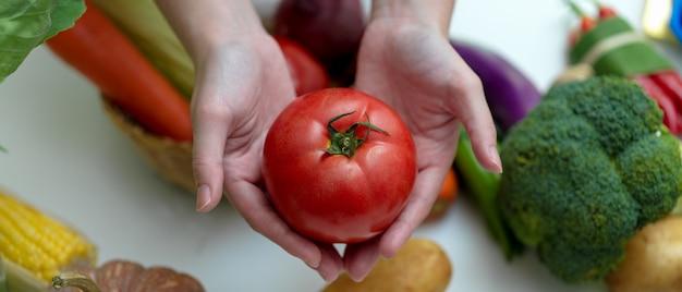 Mãos segurando o tomate em pé na mesa com outros legumes frescos da fazenda