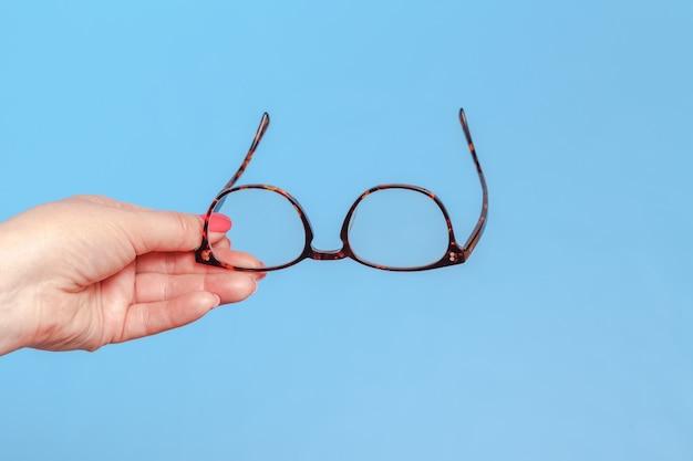 Mãos segurando óculos com estilo clássicos