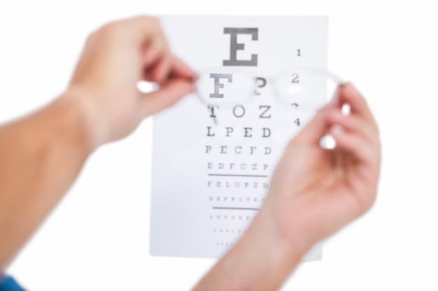 Mãos segurando óculos para teste de olho