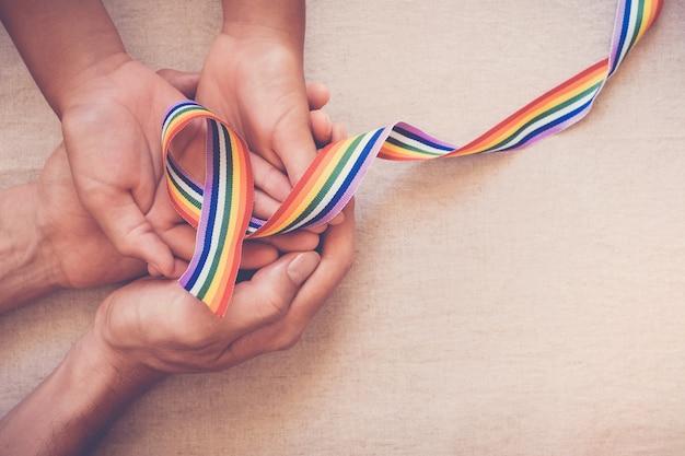 Mãos, segurando, orgulho gay, arco íris, fita, para, lgbt, consciência