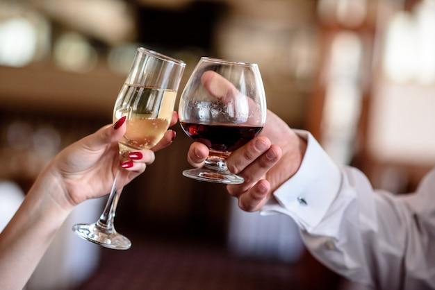 Mãos segurando os copos de conhaque e champanhe.