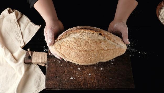 Mãos, segurando, oval, assado, pão trigo farinha, sobre, tabela madeira