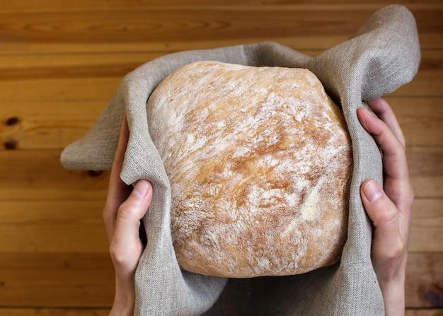 Mãos segurando pão acabado de cozer embrulhado em tecido de linho