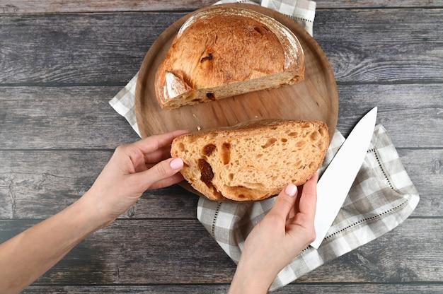 Mãos segurando pão caseiro cortado em fundo de madeira