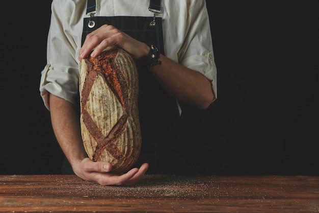 Mãos segurando pão quente fresco no fundo, foto tonificada