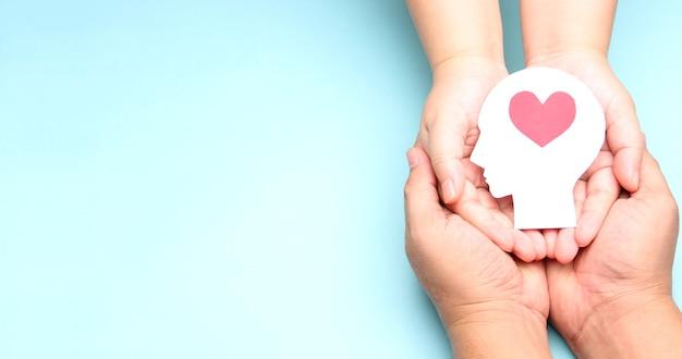 Mãos segurando papel cérebro e coração.