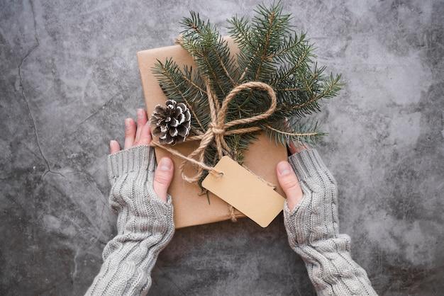 Mãos, segurando, presente, caixa, com, senhos, e, abeto, ramos