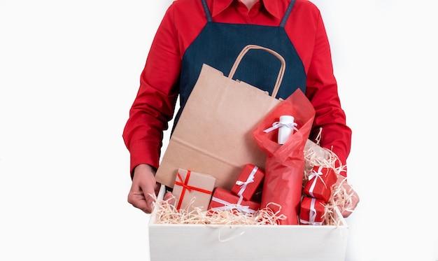 Mãos segurando presentes, sacola de embalagem e garrafa de vinho