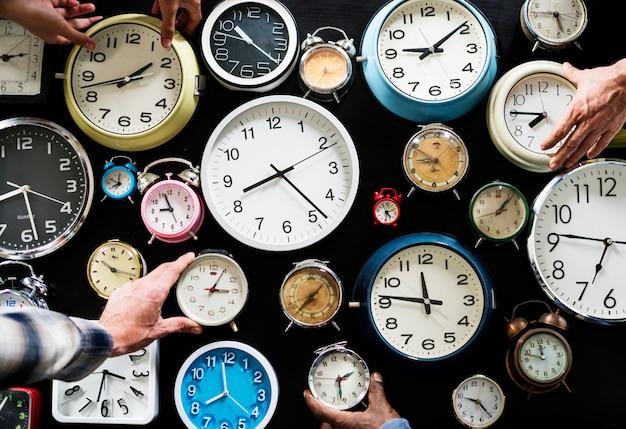 Mãos segurando relógios