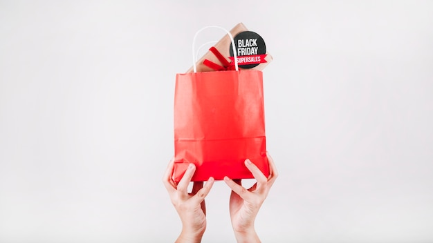 Mãos segurando saco de compras vermelho preto sexta feira