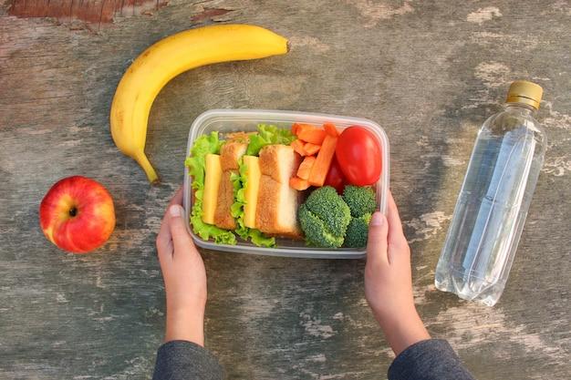 Mãos segurando sanduíches, frutas e legumes na caixa de alimentos