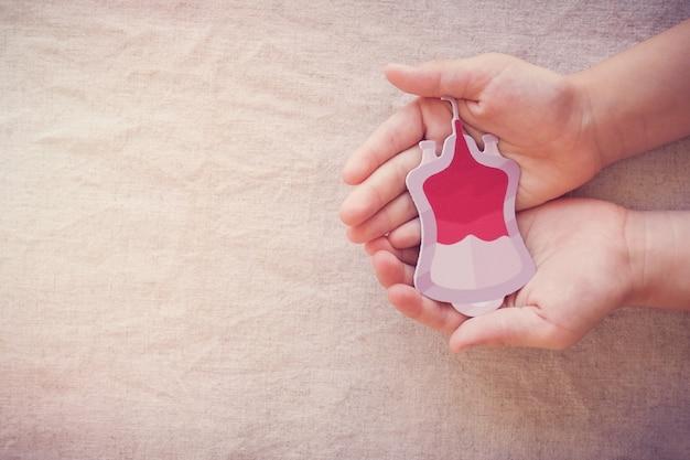Mãos segurando sangue, dê doação de sangue, transfusão de sangue, dia mundial do doador de sangue, conceito de dia mundial da hemofilia