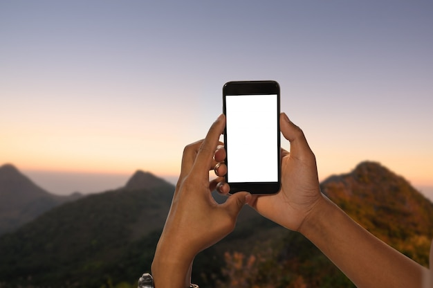 Mãos segurando smartphone maquete com tela vazia na natureza da paisagem