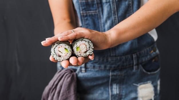 Mãos, segurando, sushi, envoltórios