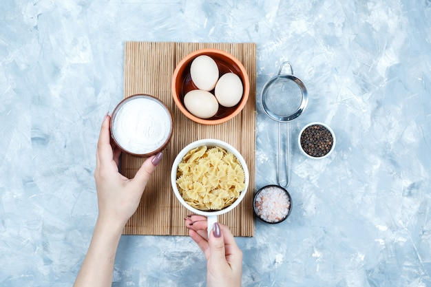 Mãos segurando tigelas de iogurte e macarrão com ovos, peneira, especiarias planas sobre fundo cinza sujo e placa de corte