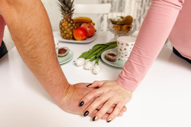 Mãos segurando um ao outro na mesa