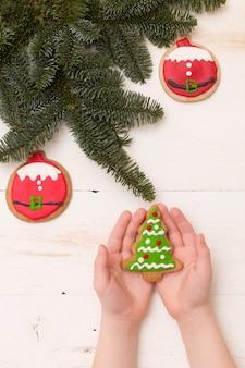Mãos segurando um biscoito caseiro de árvore de natal na mesa de madeira com ramos de abeto e enfeites