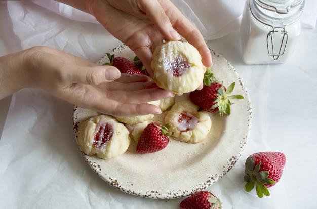 Mãos segurando um biscoito recheado com geleia de morango