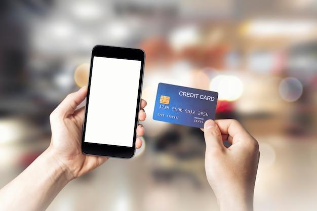Mãos segurando um cartão de crédito com celular inteligente