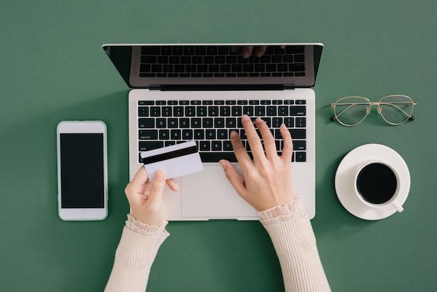 Mãos segurando um cartão de crédito de plástico e usando o laptop. conceito de compras online