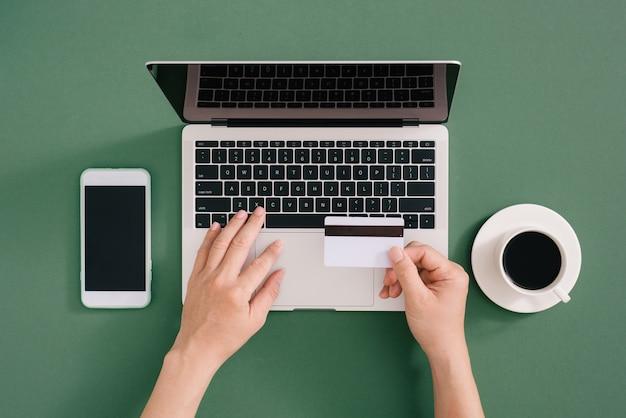 Mãos segurando um cartão de crédito, digitando no teclado do laptop, compras onine