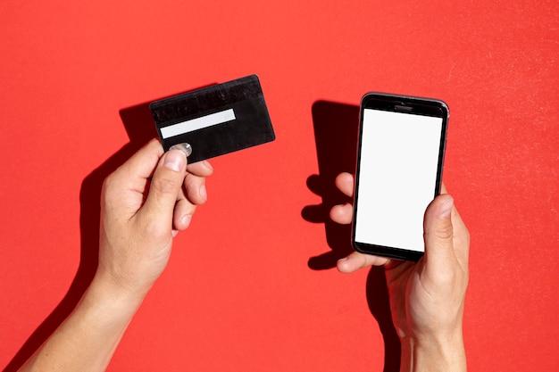 Mãos segurando um cartão de crédito e um telefone simulado