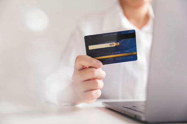 Mãos segurando um cartão de crédito e usando o computador portátil, empresária trabalhando em casa, compras on-line, comércio eletrônico, gastar dinheiro, internet banking.