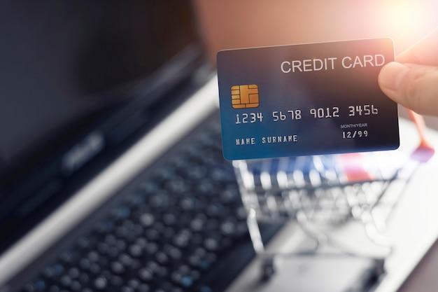 Mãos segurando um cartão de crédito e usando o laptop para fazer compras online em casa tecnologia epayment