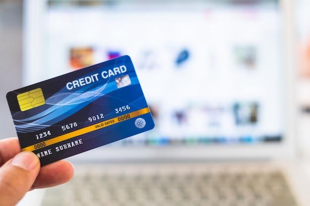 Mãos segurando um cartão de crédito e usando o laptop