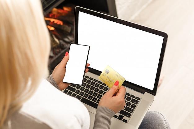Mãos segurando um cartão de crédito e usando telefone móvel esperto com manhã