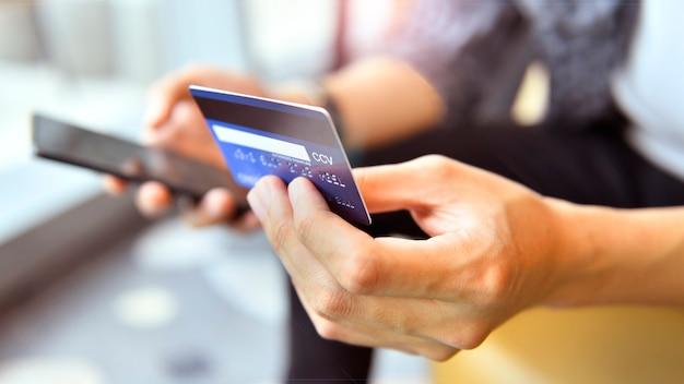 Mãos segurando um cartão de crédito e usando um smartphone para compras on-line