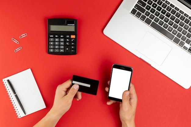 Mãos segurando um cartão e telefone simulado