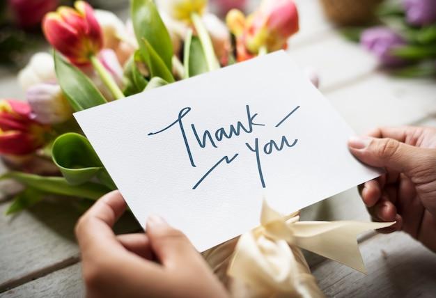 Mãos segurando um cartão vazio de espaço de design com flores de tulipas como bac