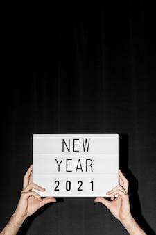 Mãos segurando um cartaz de ano novo de 2021 com espaço de cópia
