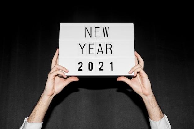 Mãos segurando um cartaz de ano novo de 2021